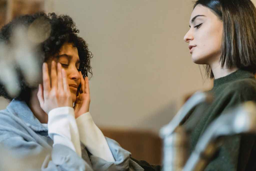 woman comforting crying black girlfriend wiping tears